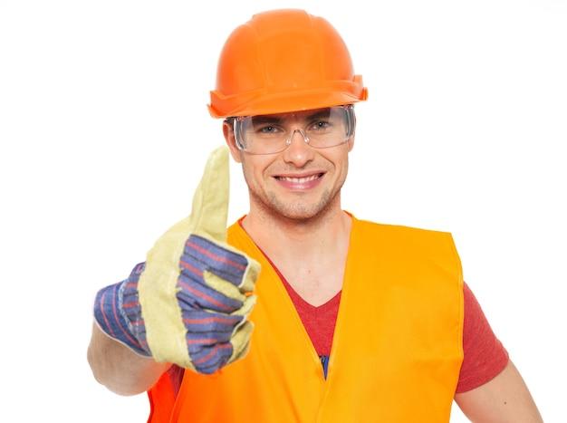 Retrato de um artesão sorridente, sinal de positivo, com uniforme protetor laranja isolado no branco