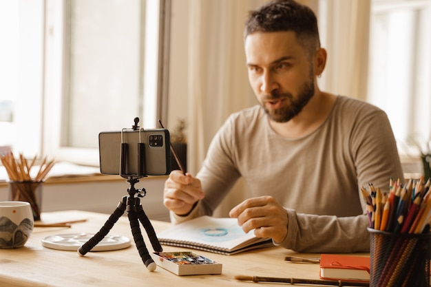 Retrato de um artista de midadult homem de cabelos escuros sorrindo feliz fazendo aula de arte online para alunos