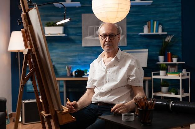 Retrato de um artista idoso, caucasiano, sentado em um estúdio de arte