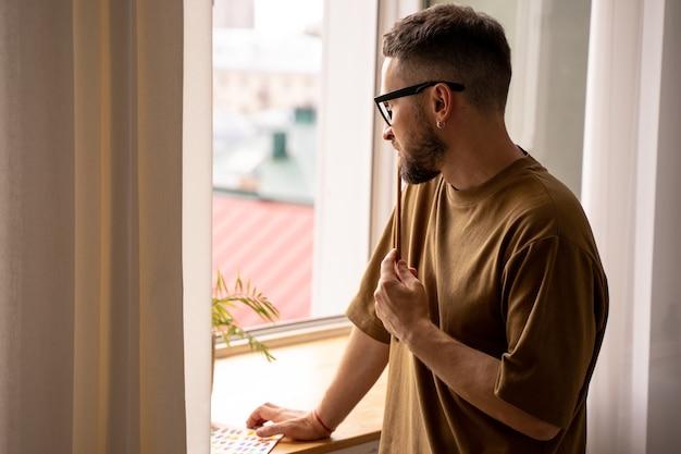 Retrato de um artista masculino em pé, olhando pela janela em busca de inspiração treinando em aulas de pintura em estúdio, dando uma aula para os alunos. pincel em uma mão. estilo de vida. emoções reais.