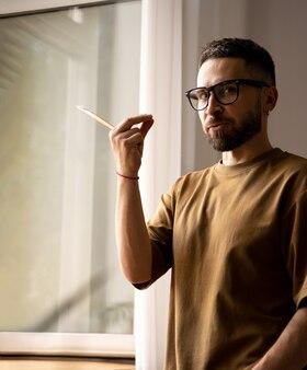 Retrato de um artista masculino em pé perto da janela treinando em aulas de pintura em estúdio dando uma aula para os alunos, gesticulando. pincel em uma mão. estilo de vida. emoções reais
