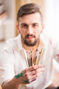 Retrato de um artista masculino novo com as escovas para pintar.