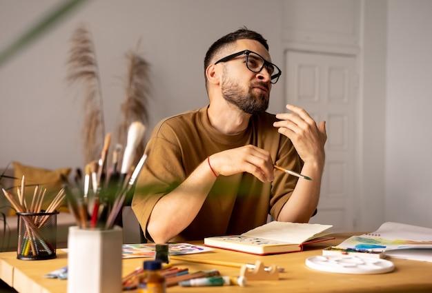 Retrato de um artista masculino sentado a uma mesa treinando em aulas de pintura em estúdio dando uma aula para os alunos, gesticulando. pincel em uma mão. estilo de vida. emoções reais.