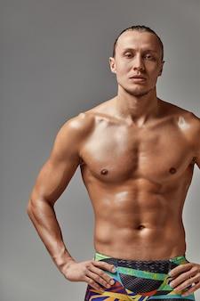 Retrato de um atleta de calção de banho, em excelente forma atlética, carismático, adulto, autoconfiante e com vontade de vencer.