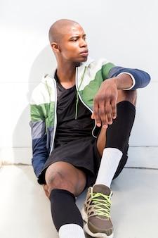 Retrato, de, um, atleta, homem jovem, sentar chão, contra, parede branca