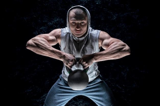Retrato de um atleta puxando um kettlebell para o queixo.