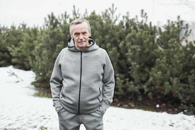 Retrato de um atleta sênior caucasiano e confiante em um terno esporte cinza em pé com as mãos nos bolsos contra árvores no inverno