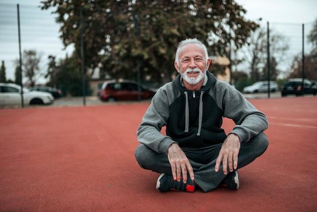 Retrato de um atleta sênior que senta-se na trilha da tartã no estádio ao ar livre.