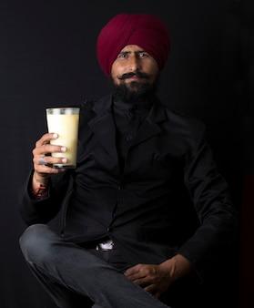 Retrato de um autêntico homem indiano punjabi sikh sorridente, usando um turbante e uma barba espessa, segurando ou bebendo lassi