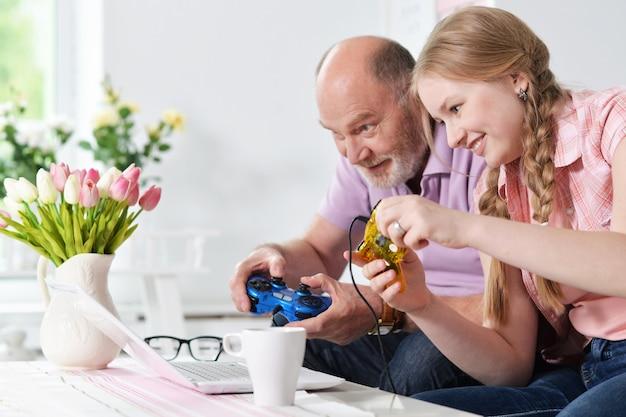 Retrato de um avô feliz e uma neta jogando videogame