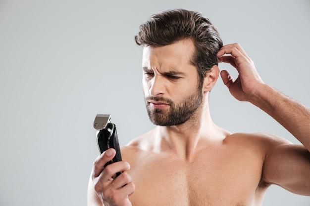 Retrato de um barbudo pensativo olhando para barbeador elétrico