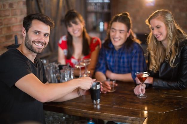 Retrato de um barman bonito a preparar bebidas para os clientes