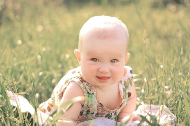 Retrato de um bebê bonito no gramado em um dia de verão