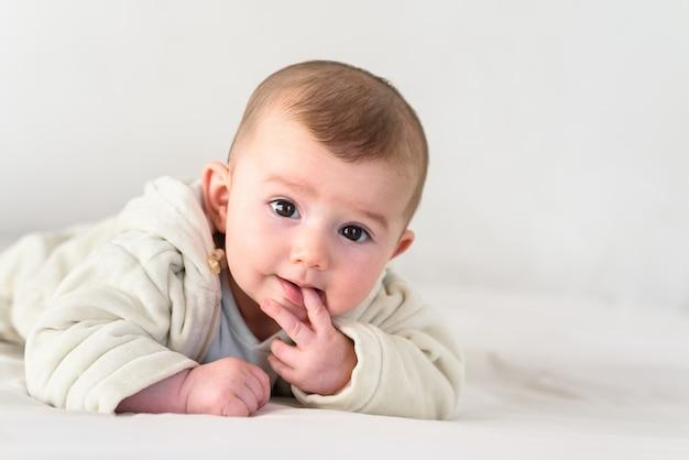 Retrato de um bebê de sorriso adorável que morde seus próprios dedos que põem seu punho em sua boca.