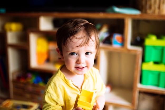 Retrato de um bebê de um ano em casa brincando com brinquedos