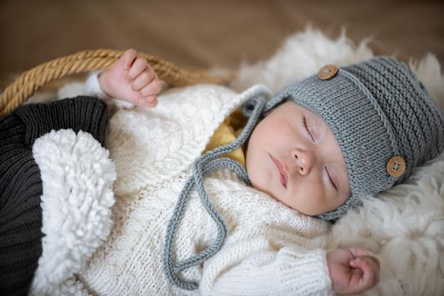 Retrato de um bebê dormindo com um chapéu de malha quente com um brinquedo de malha na alça close-up.