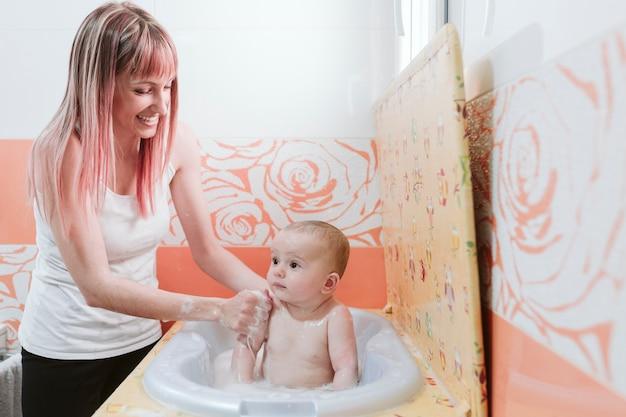 Retrato de um bebê está sendo banhado por sua mãe usando a banheira em casa
