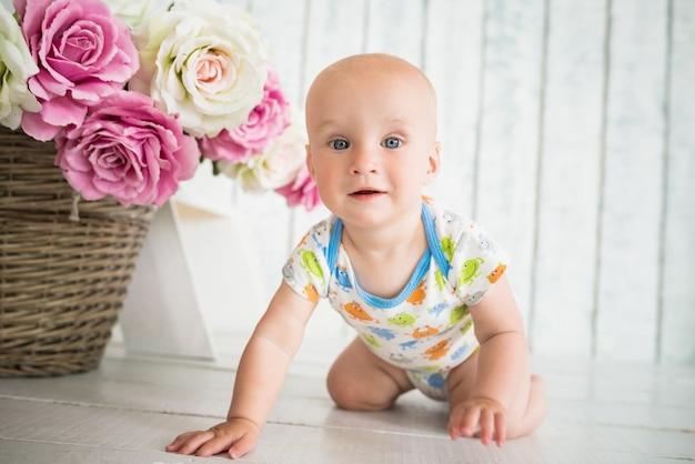 Retrato de um bebê feliz rastejando no chão. o conceito de criança saudável desenvolvida. preparando-se para os primeiros passos do bebê