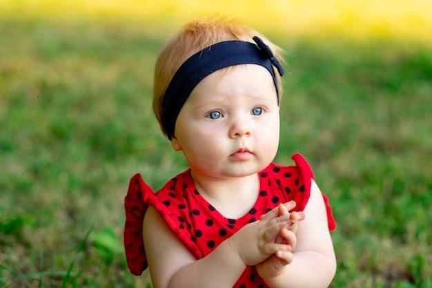 Retrato de um bebê fofo no verão na grama verde com uma roupa vermelha no sol poente