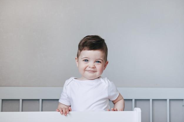 Retrato de um bebê menino engatinhando e sorrindo em body branco na cama no quarto. olhos grandes azuis. conceito de feliz infância com copyspace