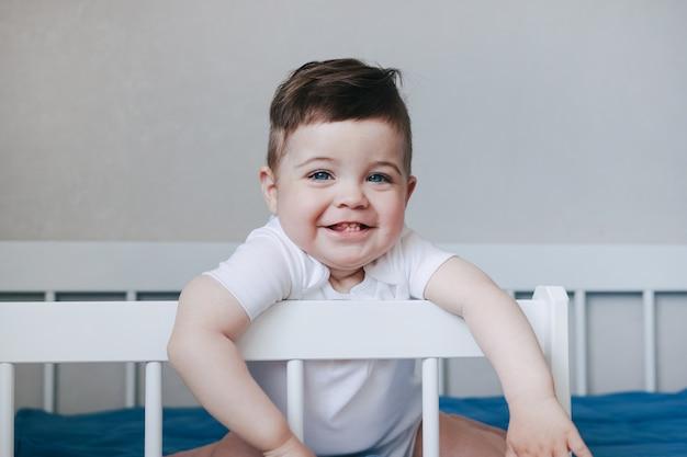 Retrato de um bebê menino engatinhando e sorrindo em body branco na cama no quarto. olhos grandes azuis. visão lateral do conceito de infância feliz