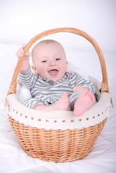 Retrato de um bebê pequeno em uma cesta.