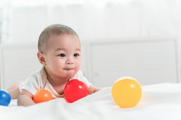 Retrato de um bebê rastejando na cama no quarto dela e jogando bola brinquedo