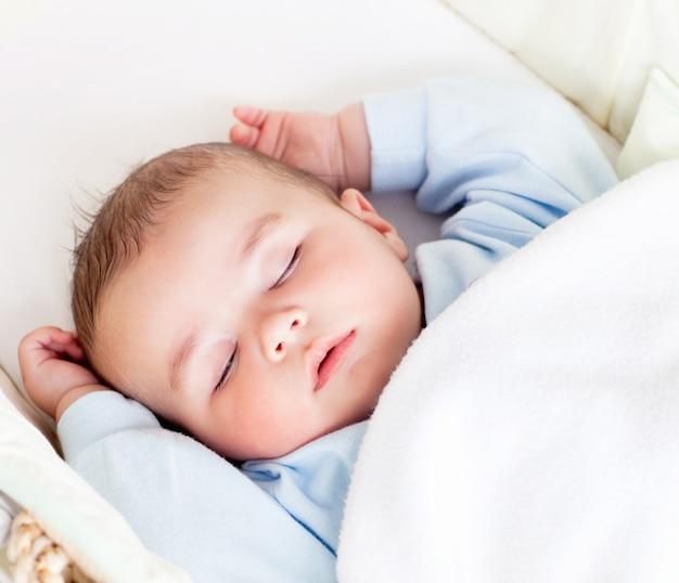 Retrato de um bebê tranquilo dormindo em seu berço em casa