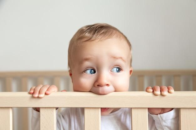 Retrato de um bebezinho fofo de olhos azuis em um macacão branco, mordendo a cabeceira da cama de madeira no fundo branco, espaço de cópia, horizontal
