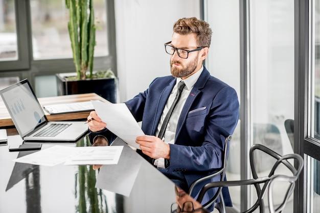 Retrato de um belo banqueiro trabalhando com um laptop sentado no interior do escritório de luxo com uma bela vista sobre os arranha-céus