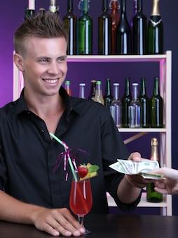 Retrato de um belo barman recebendo dicas de um cliente
