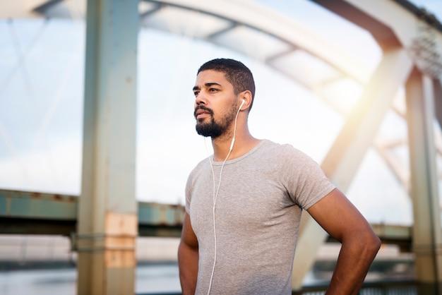 Retrato de um belo desportista com fones de ouvido se preparando para o treino