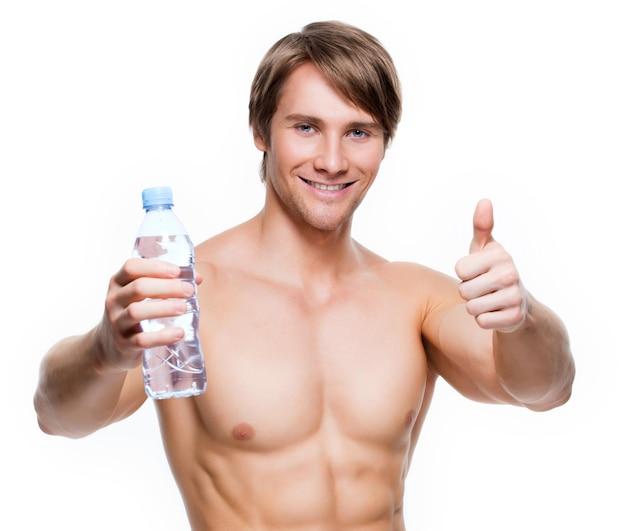 Retrato de um belo desportista musculoso sem camisa segurando água e mostrando sinal de positivo