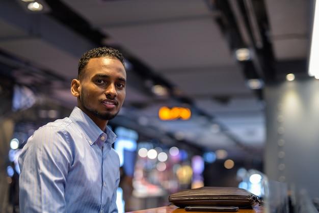Retrato de um belo empresário negro africano sentado dentro de um shopping center horizontal.