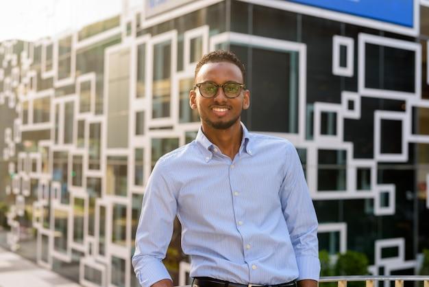 Retrato de um belo empresário negro africano sorrindo ao ar livre na cidade durante o verão