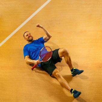 Retrato de um belo jogador de tênis celebrando seu sucesso em uma quadra