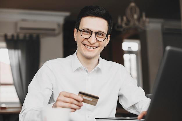 Retrato de um belo jovem gerente caucasiano sentado em um restaurante e olhando para a câmera, sorrindo, segurando um cartão dourado durante a operação em um laptop.