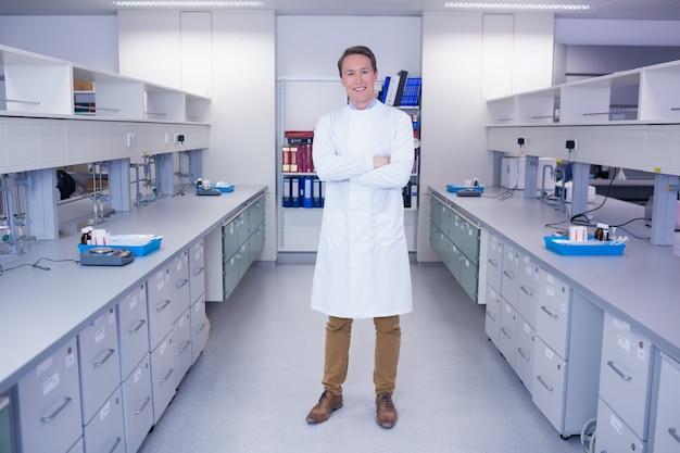 Retrato de um bioquímico sorridente de pé com os braços cruzados