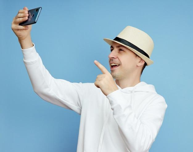 Retrato de um blogueiro de homem com um telefone na mão se comunicando em um smartphone, chamada de vídeo