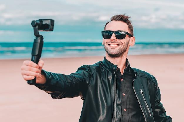 Retrato de um blogueiro sorridente em óculos de sol fazendo selfie ou streaming de vídeo na praia usando a câmera de ação com estabilizador de câmera gimbal.