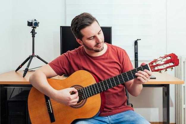 Retrato de um blogueiro tocando violão em seu estúdio de gravação em casa.