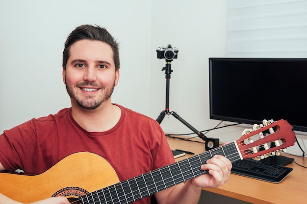 Retrato de um blogueiro tocando violão em seu estúdio de gravação em casa.