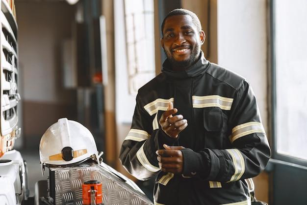 Retrato de um bombeiro em frente a um carro de bombeiros