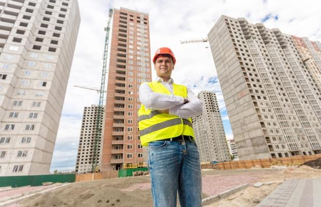 Retrato de um bonito engenheiro de construção em pé no canteiro de obras