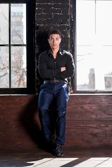 Retrato, de, um, bonito, homem jovem, inclinar-se, parede, com, seu, braços cruzaram