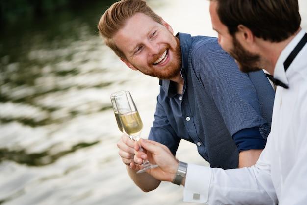Retrato de um bonito homens amigos segurando champanhe ao ar livre. casamento, festa, conceito de aniversário