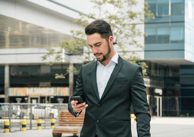 Retrato, de, um, bonito, jovem, homem negócios, fazendo, mensagem texto, ligado, telefone móvel
