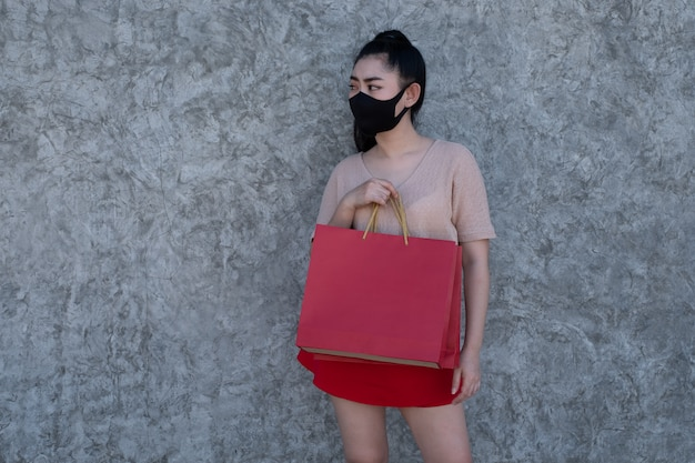 Retrato, de, um, bonito, jovem, mulher ásia, desgastar uma máscara facial, com, segurando sacolas, em, parede concreto, parede, mulheres, desgastar, cor-de-rosa, saia, e, vermelho, saia