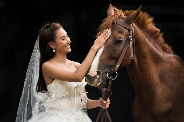 Retrato, de, um, bonito, jovem, mulher asian, noiva, e, cavalo marrom, ligado, pretas