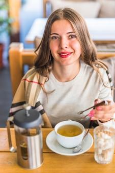 Retrato, de, um, bonito, mulher jovem, segurando, tong, em, mão, com, xícara chá herbal, ligado, tabela
